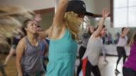 Medium panning shot of women dancing in exercise class / Orem, Utah, United States