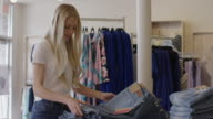 Medium panning shot of worker arranging jeans in clothing store / American Fork, Utah, United States