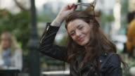 Medium panning shot of young woman removing sunglasses and smiling at sidewalk cafe / New York City, New York, United States