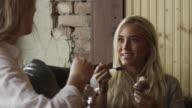 Medium panning shot of young women talking and eating ice cream / Provo, Utah, United States