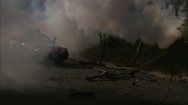 Medium pan-right - A patrol car drives through thick, billowing smoke