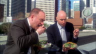 Medium shot 2 bald businessmen eating take out salads outdoors