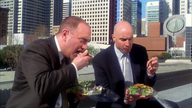 Medium shot 2 bald businessmen eating take out salads outdoors
