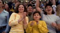 Medium shot 2 Hispanic women and Hispanic boy cheering in stadium