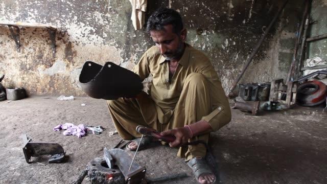 Medium shot a welder joins metal components at a workshop in Karachi Close shot metal components are welded at a workshop in Karachi