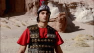 Medium shot actor dressed as Roman soldier / zoom out to reveal boom operator standing on ladder holding mic on desert film set / Red Rock Canyon State Park, California