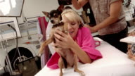 Medium shot actress on massage table having hair done and holding up dog
