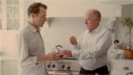 Medium shot adult son giving his father a pill as father chops vegetables in kitchen/ Solebury, PA