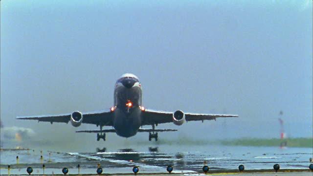 Medium shot airplane taking off / low angle landing gear folding up