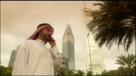 Medium shot Arab man talking on cell phone near Jumeirah Emirates Towers Hotel/ Dubai, United Arab Emirates