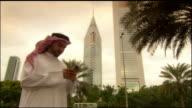Medium shot Arab man text messaging on cell phone near Jumeirah Emirates Towers Hotel/ Dubai, United Arab Emirates