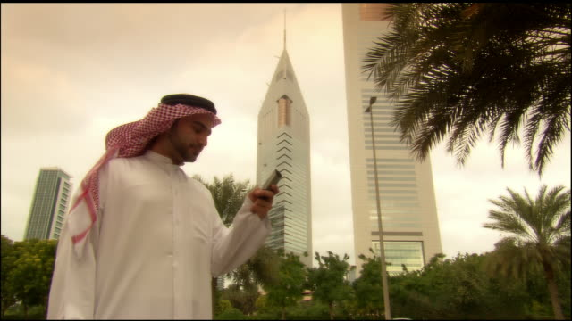 Medium shot Arab man text messaging on cell phone near Jumeirah Emirates Towers Hotel/ Dubai, United Arab Emirates