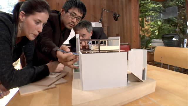 Medium shot architects looking at model of building
