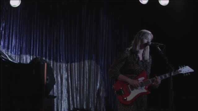 Medium shot, Ash plays guitar and sings