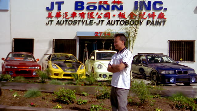 Medium shot Asian man turning to look at front of autobody business w/sign / turning toward CAM