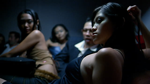 Medium shot Asian woman leaning back at nightclub / other women and man in background / Indonesia