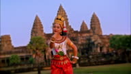 Medium shot Asian woman wearing traditional dress and dancing with temple of Angkor Wat in background / Cambodia