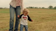 Medium shot baby boy walking in field with older girl / baby falling and getting back up / starting to cry