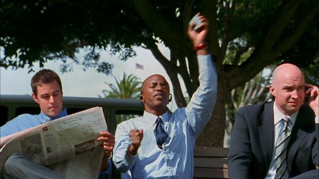 Medium shot bald black businessman singing along with walkman / skateboarder passing in foreground