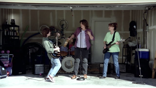 Medium shot band of middle aged women performing in garage / garage door closing