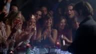 Medium shot bartender mixing drinks / customers applauding