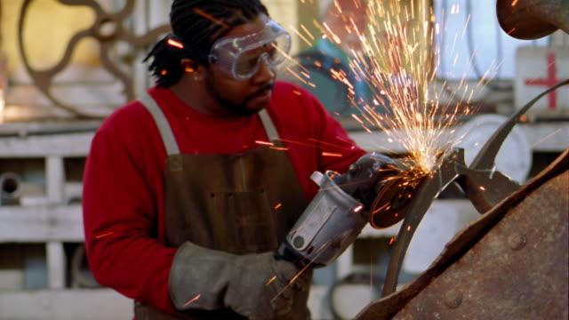 Medium shot Black artist wearing goggles sanding metal sculpture w/sparks flying off in studio