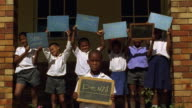 Medium shot Black boys and girl holding up chalkboard with names written on them outdoors / South Africa