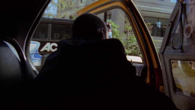 Medium shot Black businessman stepping out of taxicab