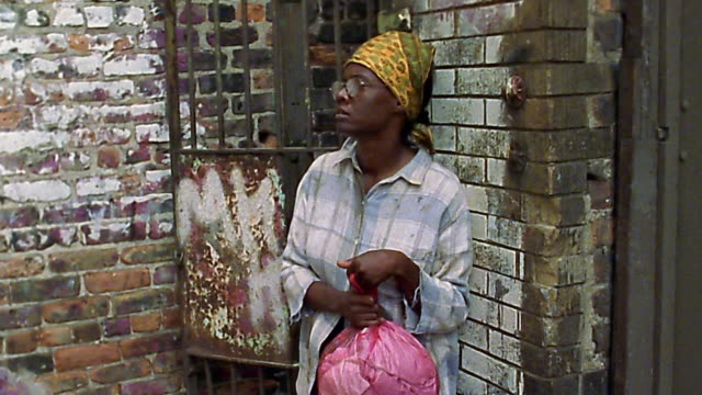 Medium shot Black homeless woman holding plastic bag next to brick wall