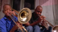 Medium shot Black man playing trumpet & boy playing trombone on front porch of house / New Orleans