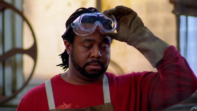 Medium shot Black metal sculptor in apron lifting his goggles and smiling at CAM