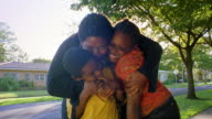 Medium shot Black mother hugging and kissing son + daughter