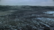 Medium shot boat point of view sailing on rough sea on overcast day / Arctic