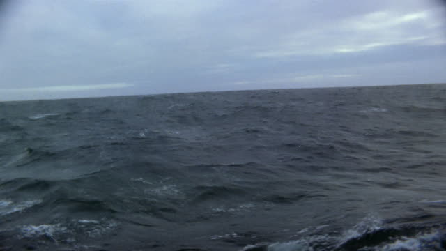 Medium shot boat point of view waves in rough sea on overcast day / Arctic