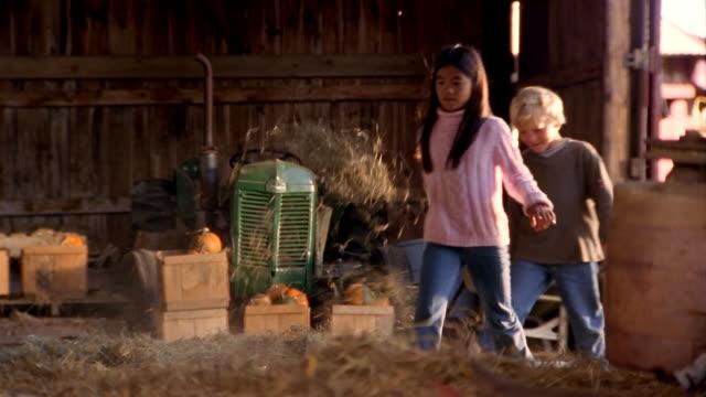 Medium shot boy and girl kicking through piles of hay