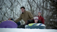 Medium shot boy and girl sledding down snow-covered hill on inner tubes / father giving daughter a push