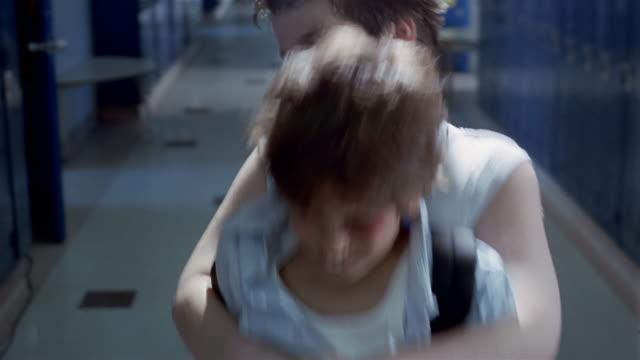 Medium shot boy bullying smaller boy in hallway of junior high school