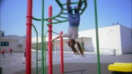 Medium shot boy hanging upside down on monkey bars and smiling / girl hanging upside down in background