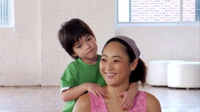 Medium shot boy hugging and kissing mother/ Brooklyn, New York