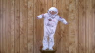 Medium shot boy in astronaut space suit costume posing on pedestal w/wood paneling in background