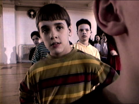 Medium shot boy in line in gym class raising fists and giving excited expression/ New York City