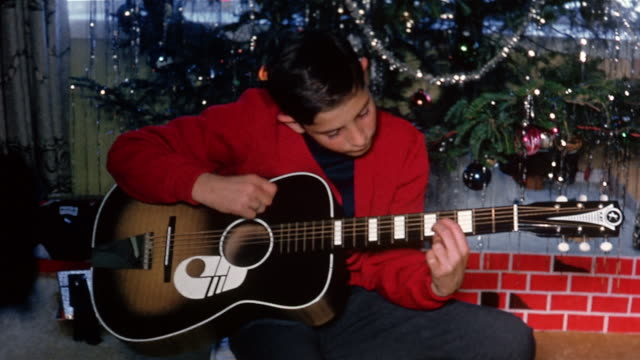 1966 medium shot boy in red blazer looking at CAM and playing guitar in front of Christmas tree