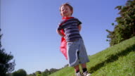 Medium shot boy in red superhero cape standing outdoors and looking at CAM w/cape blowing in wind