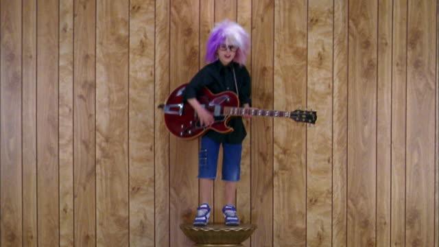 Medium shot boy in rock star costume on pedestal pretending to play electric guitar