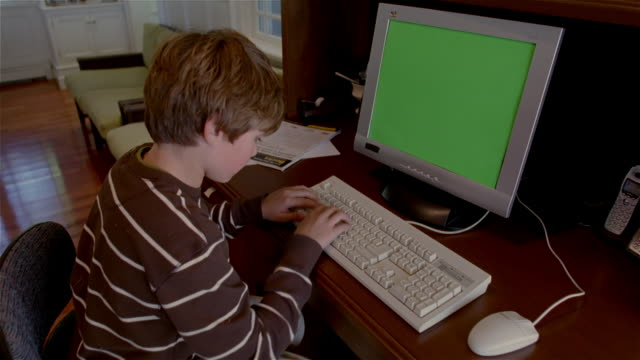 Medium shot boy typing on PC with green screen on monitor/ Solebury, Pennsylvania