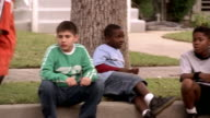 Medium shot boys sitting on curb watching other kids play soccer / celebrating a goal