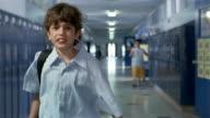 Medium shot bully following boy down empty hallway of junior high school