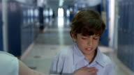 Medium shot bully taking boy's lunch money in empty hallway of junior high school
