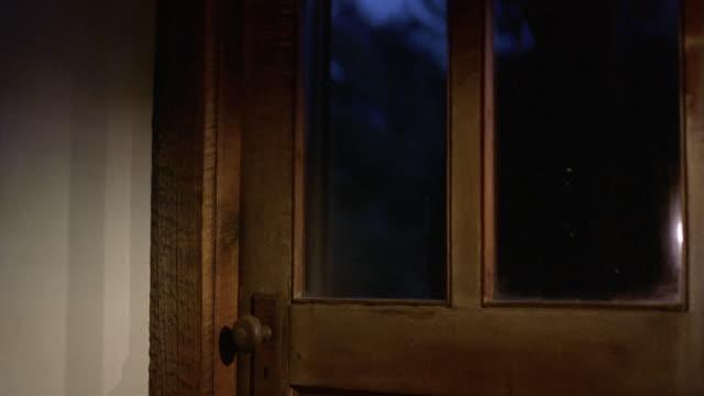 Medium shot burglar smashing window on window / reaching in to open door from inside