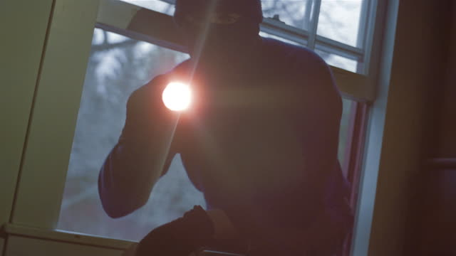 Medium shot burglar with flashlight looking around house/ climbing in through window